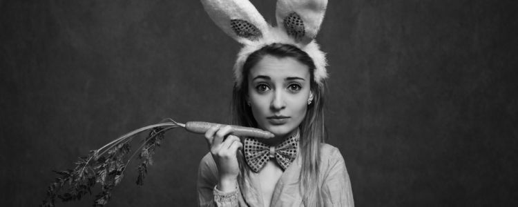 A young woman holding a carrot in bunny outfit - looking at the camera - vignetting, brown tone and film grain was added for the mood